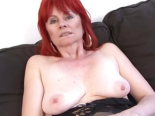 Red haired granny in erotic lingerie is having casual lovemaking with a black guy, on the sofa